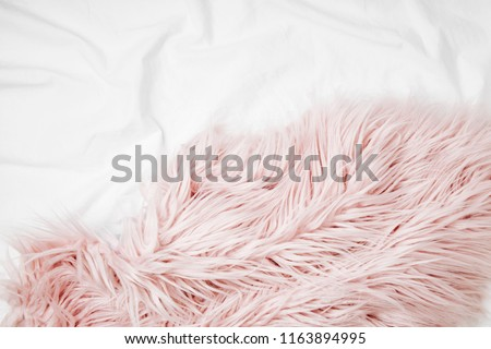Bedding with a pink fluffy fur plaid. Copy space. Flat lay, top view