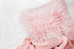 Bedding with a pink pillow and knitted plaid. Copy space. Flat lay, top view