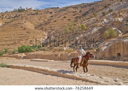 Bedouin horseman rides the ancient roadway into Petra, Jordan