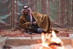 Bedouin man wearing traditional clothes praying with a tasbih while drinking tea on a carpet in front of a fire in the Saudi desert, Saudi Arabia