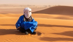 Bedouin sitting on the sand in the Sahara desert