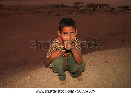 BEDOUIN VILLAGE IN SINAI MOUNTAINS, EGYPT - MARCH 9: Unidentified barefoot boy from bedouin village at dusk trying to sell own made bracelet - 9 March 2010 in Egypt