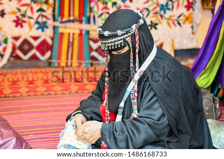 Bedouin Woman wears traditional Arabic Clothes doing kraft hand made Sado in Hijin festival activity in Taif City in Saudi Arabia. Mawsim Al Taif Stock fotó ©