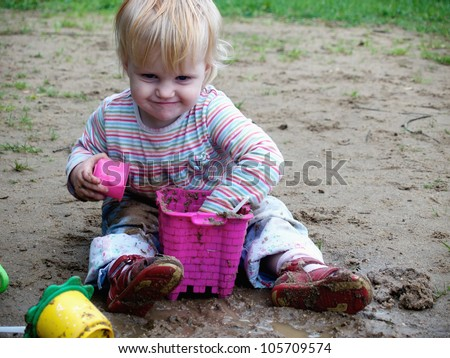 bedraggled baby play with  sand - stock photo