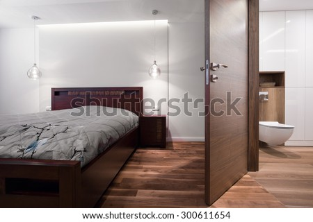 Bedroom connected with bathroom in wooden house