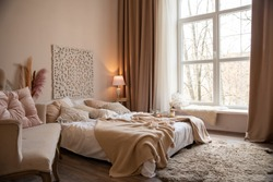 Bedroom in beige tones with a large bed and a large window through which a lot of light penetrates. Minimal style in the interior. Convenient and practical location of furniture, cozy view.