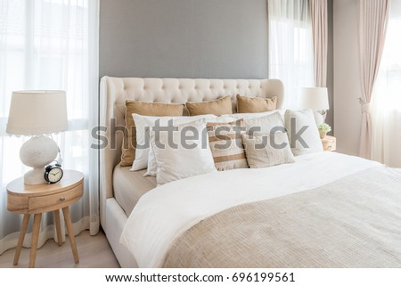 Bedroom in soft light colors. big comfortable double bed in elegant classic bedroom at home. #696199561