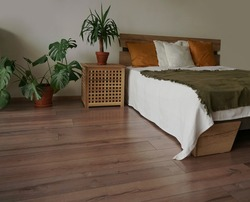 bedroom in soft light colors. big comfortable double bed in elegant classic bedroom. many green plants. natural wooden materials.