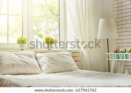 Bedroom in soft light colors. Big comfortable double bed in elegant classic room. #627965762
