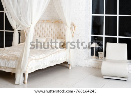 Bedroom in soft light colors. Big comfortable four poster double bed in elegant classic bedroom. Luxury elegant white with gold interior design.