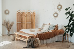 Bedroom interior in Bohemian style with patterned bed. Home interior detail in Boho style