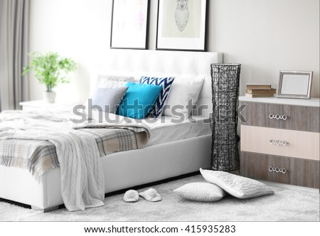 Bedroom interior in light tones with white furniture and pictures on the wall #415935283