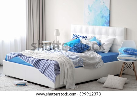 Bedroom interior in light tones with white furniture and pillows