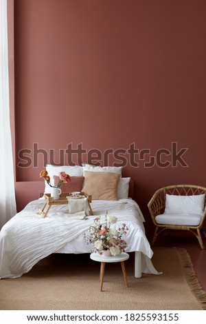 Bedroom interior of wicker armchair, bed and small wicker table on it for breakfast with a pink wall in the background