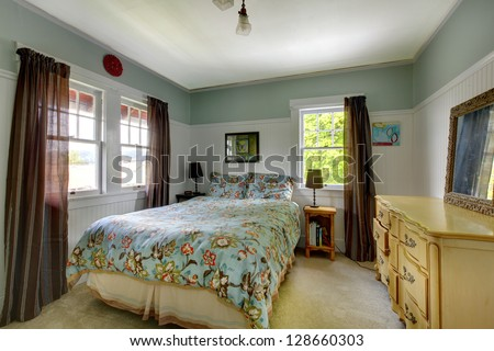 Bedroom interior with blue and brown, dresser and carpet.