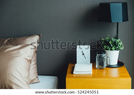 Bedroom interior with clock, lamp and plant pot on wooden table