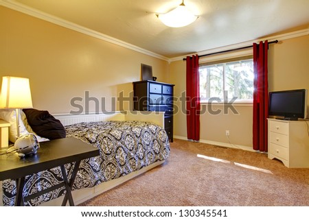 Bedroom interior with yellow walls , black dresser and TV.