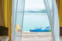 Bedroom view with kayak on a lake and mountain with window curtains.