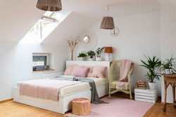 Bedroom with bed in cozy interior in white and pink color. Scandinavian style in room in the attic with double bed.