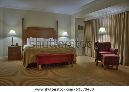 Bedroom with bedside tables armchair lamps and curtain - stock photo