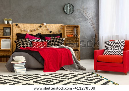 Bedroom with big bed, DIY furniture, pattern carpet and red armchair