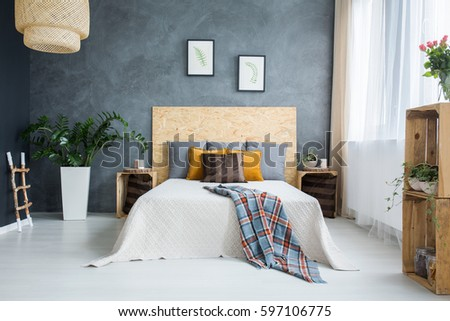 Bedroom with concrete wall, bed, lamp and plants #597106775