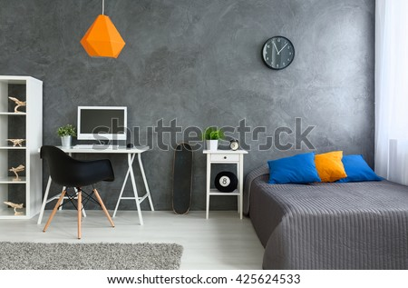 Bedroom with grey walls and grey bed with  colorful pillows and orange lamp. By the wall skate board and desk with computer #425624533