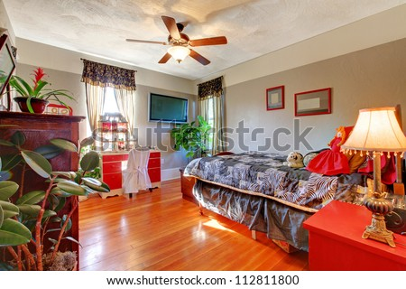 bedroom with hardwood floor and grey walls with red desk stock photo