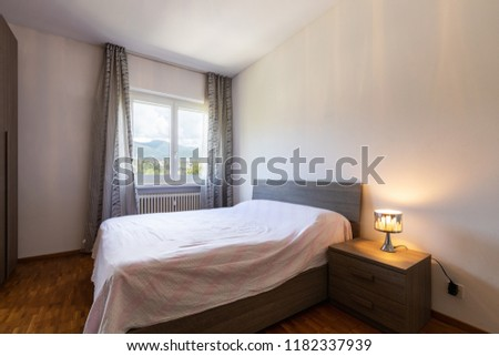 Bedroom with parquet and window with view. Nobody inside