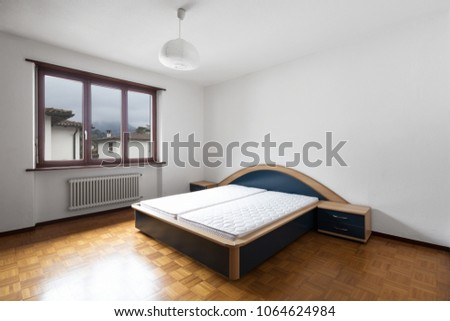 Bedroom with parquet, bed without blankets. Nobody inside #1064624984