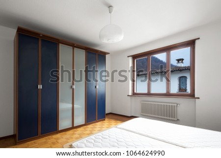 Bedroom with parquet, bed without blankets. Nobody inside #1064624990