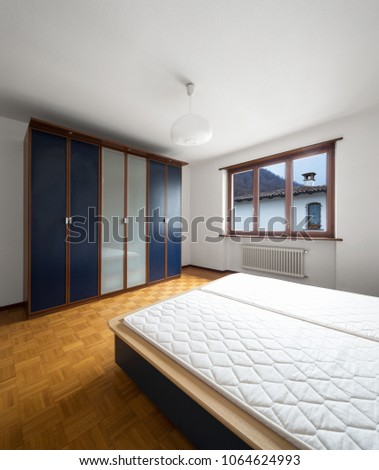 Bedroom with parquet, bed without blankets. Nobody inside #1064624993