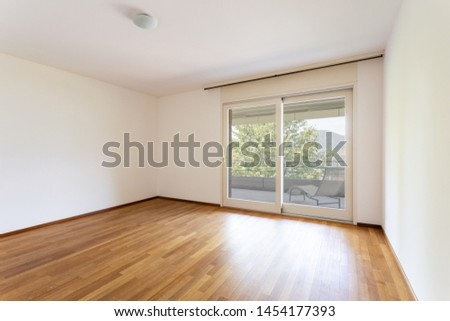 Bedroom with white walls and parquet. Window with lake view. Nobody inside