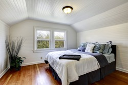 Bedroom with wood plank paneled walls and ceiling. View of black queen size bed and dry branches in the corner