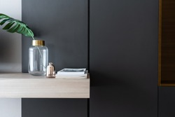 Bedroom working corner decorated with books and artificial plant in a gold collar glass vase on gray spray-painted wardrobe wall/apartment interior detail /copy space / modern style