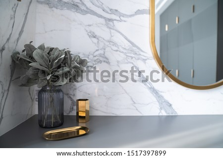 Bedroom working corner decorated with hexagon gold stainless vase and artificial plant in glass vase on gray spray-painted  working table with  marble wall in the background /apartment interior