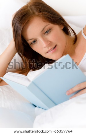 Bedroom - young woman read book in white bed