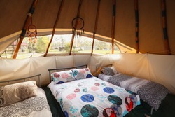 Beds set up inside tipi with light coming in and dream catchers hanging in the window