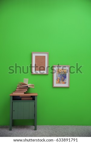 Bedside table with books and paintings on greenery wall background #633891791