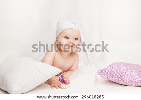 Bedtime. Baby in pyjamas with pillow in bedroom.