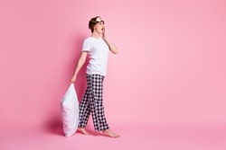 Bedtime concept. Full length profile photo of pretty lady hold pillow sleepy tired walk to bed wear sleep mask white t-shirt checkered pajama pants barefoot isolated pink color background