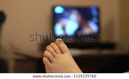 Bedtime relaxation. Woman feet relaxing lying in bed and watching TV