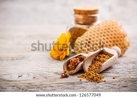 Bee pollen granules and propolis in wooden scoop