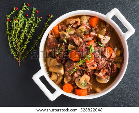 Beef Bourguignon in a casserole on black stone. Stewed with bacon, garlic, carrots, onions, mushrooms,  red wine, fresh thyme and spices. Top view