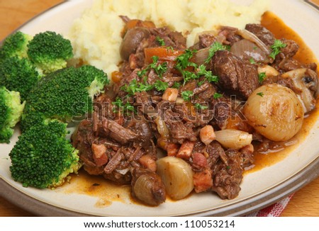 Beef bourguignon stew served with broccoli and mashed potato.
