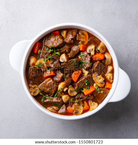 Photo of  Beef bourguignon stew with vegetables. Grey background. Top view.