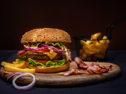 Beef burger and french fries on wooden table isolated on black background