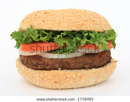 Beef burger in a bun, over white, with lettuce salad, tomato, onion, close up, macro