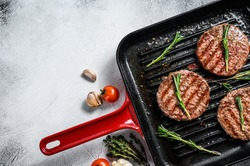 Beef burger patties sizzling on a hot barbecue pan. White background. Top view. Copy space