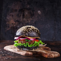 Beef burger with a black bun,with lettuce and mayonnaise and ketchup served on pieces of brown paper on a rustic wooden table of counter, on a dark background.selective focus